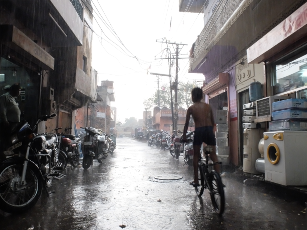 child_riding_under_the_rain